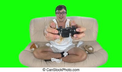 Gamer playing video games with gamepad sitting on filthy couch