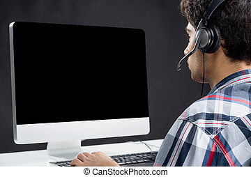 Gamer. Rear view of teenager playing video games at his...