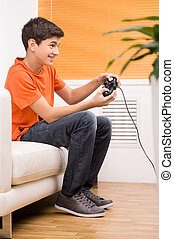 Gamer with joystick. Young gamer playing video games while sitting on the couch