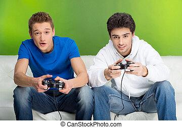 gamers, עם, joystick., שני, צעיר, gamers, לשחק משחקי וידאו, בזמן, לשבת על הספה