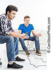 gamers, sitzen, junger, freigestellt, joystick., während, video, zwei, spiele, weißes, couch, spielende
