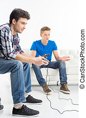 Gamers with joystick. Two young gamers playing video games while sitting on the couch isolated on white