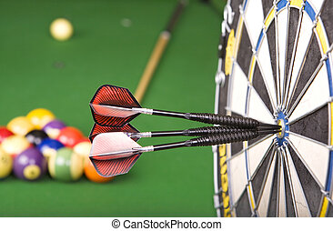 Games - darts in a dart board with a pool game in the...