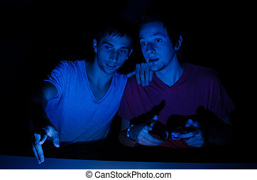 Two friends in front of a computer screen gaming