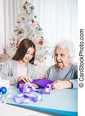 Ganddaughter helping grandma decorating gifts