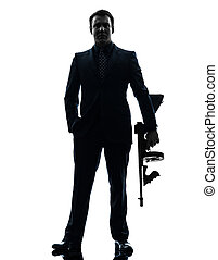 gangster man holding thompson machine gun silhouette - one...