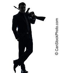 gangster man holding thompson machine gun silhouette