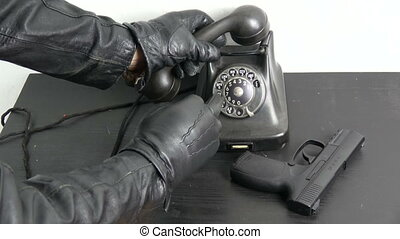 Gangster robber hand with black leather glove dialing...