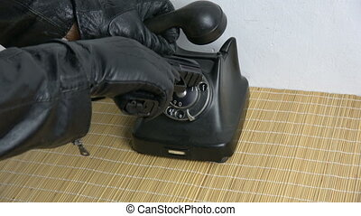 Gangster thief hand with leather glove dialing ancient telephone dial disc with hand gun pistol