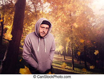Gangster waiting for victim in autumn park