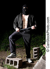 Gangster with baton outdoors at night