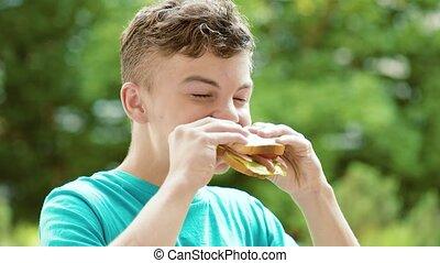 garçon adolescent, sandwich, manger