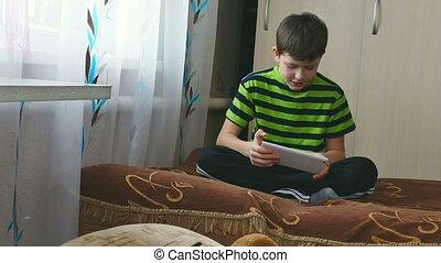 garçon, adolescent, tablette, séance, divan, jouer