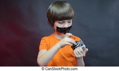 garçon, bande, bouche, appareil-photo., vieux, sien, sur, examine, noir