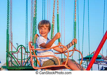 garçon, chaîne, cavalcade, avoir, carousel., park., enfant, amusement, prendre, amusement, heureux