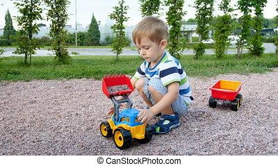garçon, chargement, mignon, chargeur, park., vidéo, 4k, jouet, gravier, jouer, enfantqui commence à marcher, caravane, cour de récréation