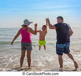 garçon, famille, tenant mains, plage, heureux