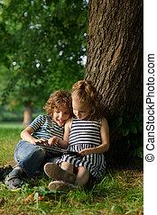garçon, jeu, 7-8, asseoir, tablet., arbre, années, sous, la terre, girl
