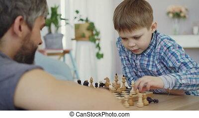 garçon, jeu, dad., premier plan., intelligent, peu, figure, père, chesspieces, sien, en mouvement, échecs, apprentissage, apprécier, barbu, jouer, planche