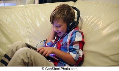 garçon, jeux, tablette, séance, sofa, écouteurs, jeune, quoique, musique, maison, heureux, écoute