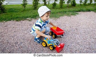 garçon, jouet, mignon, métrage, parc, chargeur, 4k, enfantqui commence à marcher, jouer, caravane