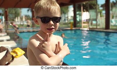 garçon, motion., lent, peu, portrait, fond, lunettes soleil, sourire, piscine