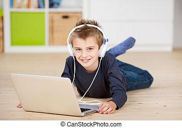 garçon, ordinateur portable, écouteurs, par, écoute, musique