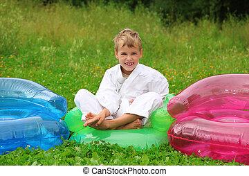 garçon, pelouse, fauteuil, gonflable, karaté, assied