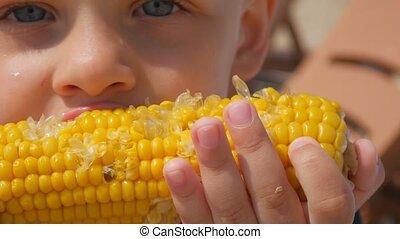 garçon, peu, bouilli, manger, corn., maïs, affamé, foyer, sea., close-up., plage