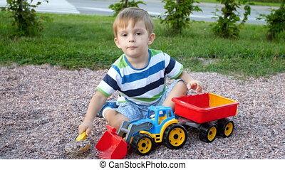 garçon, peu, chargement, jouer, jouet, vidéo, 4k, gravier, enfantqui commence à marcher, caravane, cour de récréation