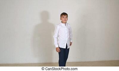garçon, peu, chemise, gai, arrière-plan., sauter, noir, pantalon blancs