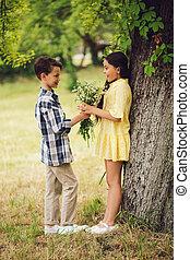 garçon, peu, donner, bouqet, girl., fleurs