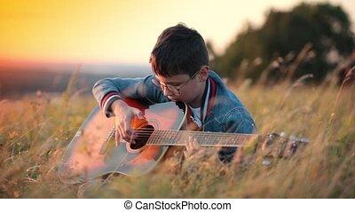 garçon, peu, jeux, guitare, arrondissez lunettes