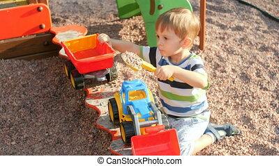 garçon, peu, jouet, tracteur, métrage, plastique, sandbox, 4k, enfantqui commence à marcher, jouer, caravane