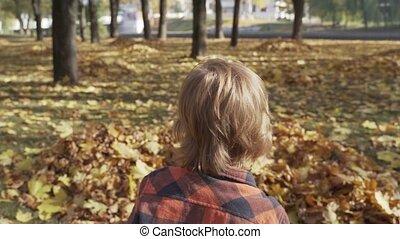garçon, peu, lancement, feuilles, parc, automne, jouer, heureux