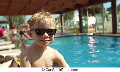 garçon, peu, lent, lunettes soleil, motion., fond, portrait, sourire, piscine