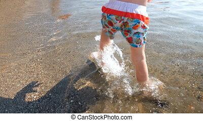 garçon, peu, métrage, marche, pieds, closeup, 4k, mer, enfantqui commence à marcher, plage