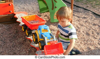 garçon, peu, pelle, sandbox, plastique, sable, chargement, vidéo, 4k, jouet, gravier, jouer, enfantqui commence à marcher, caravane