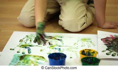 garçon, peu, plancher, feuilles, papier, handprints, assied