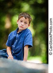 garçon, peu, séance, regarder, appareil photo, dehors, expression sérieuse
