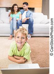 garçon, peu, salle, utilisation, séance, sofa, ordinateur portable, tapis, parents, maison, vivant, heureux
