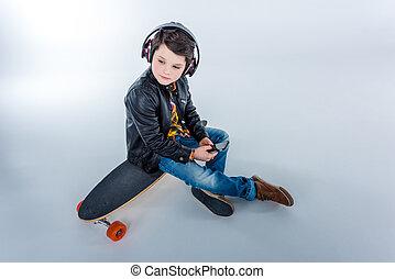 garçon, peu, songeur, séance, loin, écouteurs, skateboard, regarder