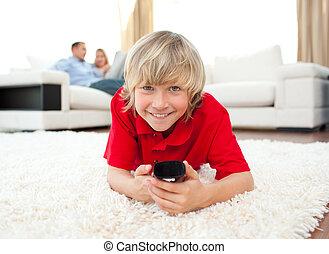 garçon, plancher, télé regarde, sourire, mensonge