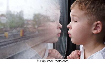 garçon, pluvieux, regarder, fenêtre, train, temps, curieux, dehors