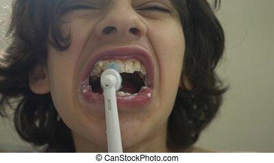 garçon, sien, électrique, 4k., brosse dents, brosses, nettoie, dents, miroir, adolescent, enfant, devant, tir, gros plan, ralenti