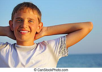 garçon, tête, mer, contre, derrière, adolescent, tenant mains, sourire