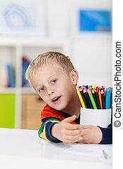 garçon, table, crayons colorés