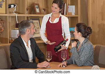 garçonete, mostrando, garrafa vinho, para, jantar, par