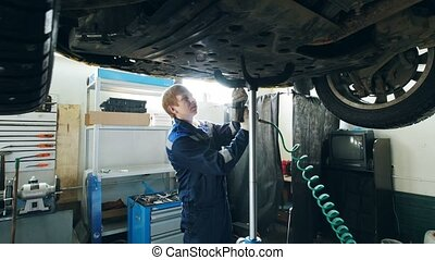 Garage auto service - mechanic unscrewing the bottom of the...