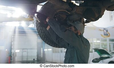 Garage automobile service - a mechanic under bottom of car checks the wheel, close up